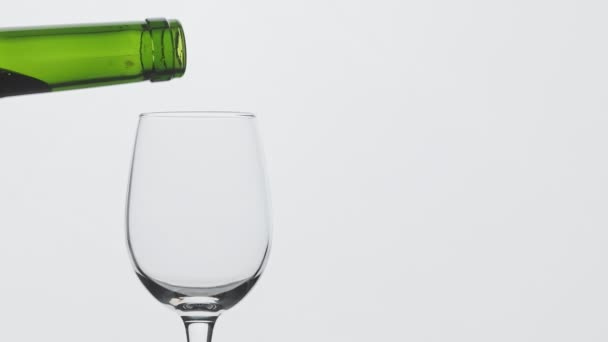 Slow motion of pouring red wine from bottle into goblet with copy space at right. Close-up of red wine forms beautiful wave in glass. Wine pouring in glass at white background.