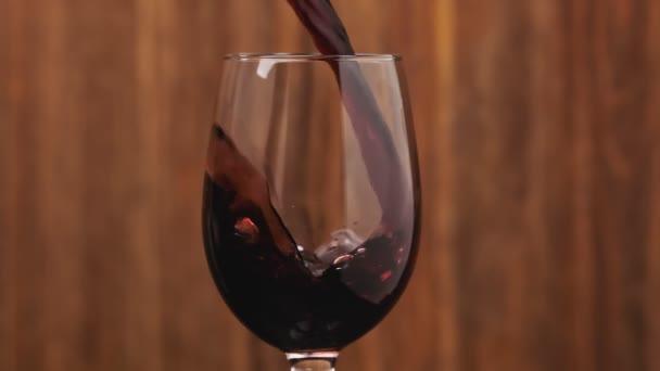Růžové víno z láhve. Sommelier nalévá výborné červené víno ve skle. Těsné doplňování vína na dřevěné pozadí. Středové složení.
