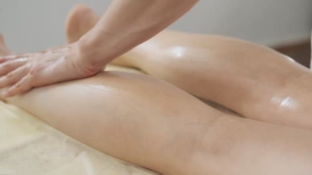 Nahaufnahme der Hände des Massagetherapeuten. Massage der menschlichen Wadenmuskulatur. Masseur knetet Fuß und Bein einer jungen Frau. Hautpflege, Wellness, Lifestyle
