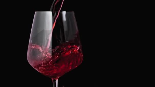 Vörösbor öntéssel a borospohár sötét háttér. Közelkép lövés a másolási hely a jobb oldalon. Lassú mozgás a szakadó vörösbor a goblet. Vörösbor képez gyönyörű hullám