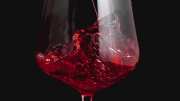 Červené víno vytváří krásnou vlnu. Víno nalévající se ve sklenici vína na černém pozadí. Záběr zblízka. Zpomalený pohyb nalévání červeného vína z láhve do poháru. Malá klávesa
