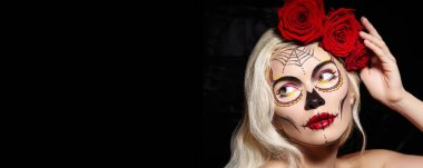 Halloween Make-Up Style. Blond Model Wear Sugar Skull Makeup with Red Roses. Dia de los Muertos or Santa Muerte concept