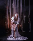 die Banshee Fee. blassblondes Mädchen im weißen Vintage-Kleid. verführerische Prinzessin, mit sexy, langen Beinen, die vor dem Hintergrund eines fabelhaften Interieurs posieren, das mit Stücken von Schleierstoff verziert ist.