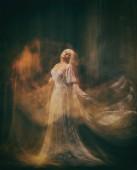 Sklavin, Dienerin der Finsternis... Königin Albino. ein blondes Mädchen, wie ein Gespenst, in einem weißen Vintage-Kleid, in einem schwarzen Zimmer, eine gotische, künstlerische Fotografie einer Zauberin und Magierin. Maria Magdalene
