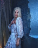 Fotografie Sexy, gothic, snow queen in a white vintage dress. A blond girl with very long hair posing against a wall near a window. Gothic photography in cold colors. The Legend of the Banshee. Artistic photo.