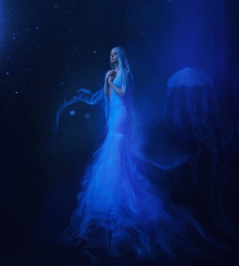 A white mermaid, with very long and blue hair floating under the water. An unusual image, the tail of a jellyfish. Levitation and weightlessness. Pale skin, gentle makeup. Art photo.