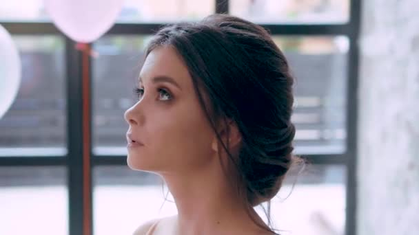 Attractive brunette with childish face and perfect healthy skin, alluring soft features, looks up, lowers her eyes, gently runs her hand over neck and chest, near the huge window and white balloons
