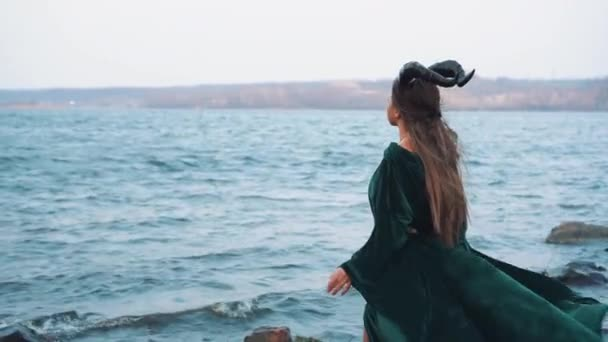 Mystic lady with long hair in flying gorgeous green dress, witch in emerald  velor gown on shore of magical lake, girl stranger changes wind and weather  with spell and magic, from back without face