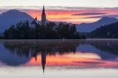 Dramatické východ slunce na jezeře Bled, sunrise výhled na jezero Bled, ostrov, poutní kostel Nanebevzetí Marie a hrad s pohoří (Stol, Vrtaca, Begunjscica). Bled, Slovinsko,