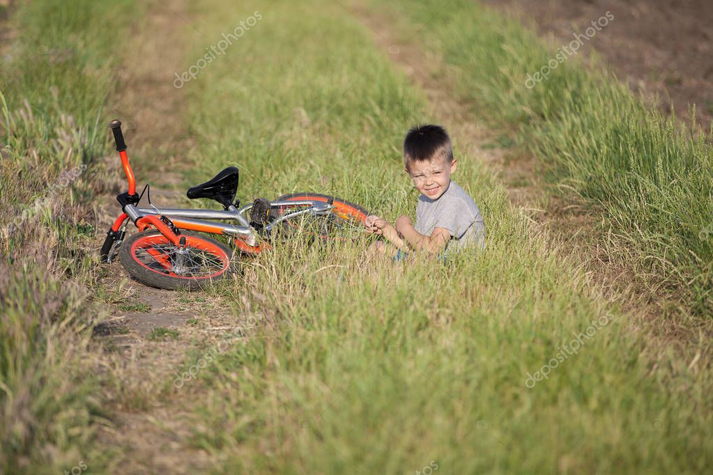 A beautiful boy is sitting in the grass. Next to him lies his bicycle. A sports kid on a walk.