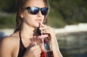 Fotografie Letní portrét dívky v brýle, který pije koktejl na pláži