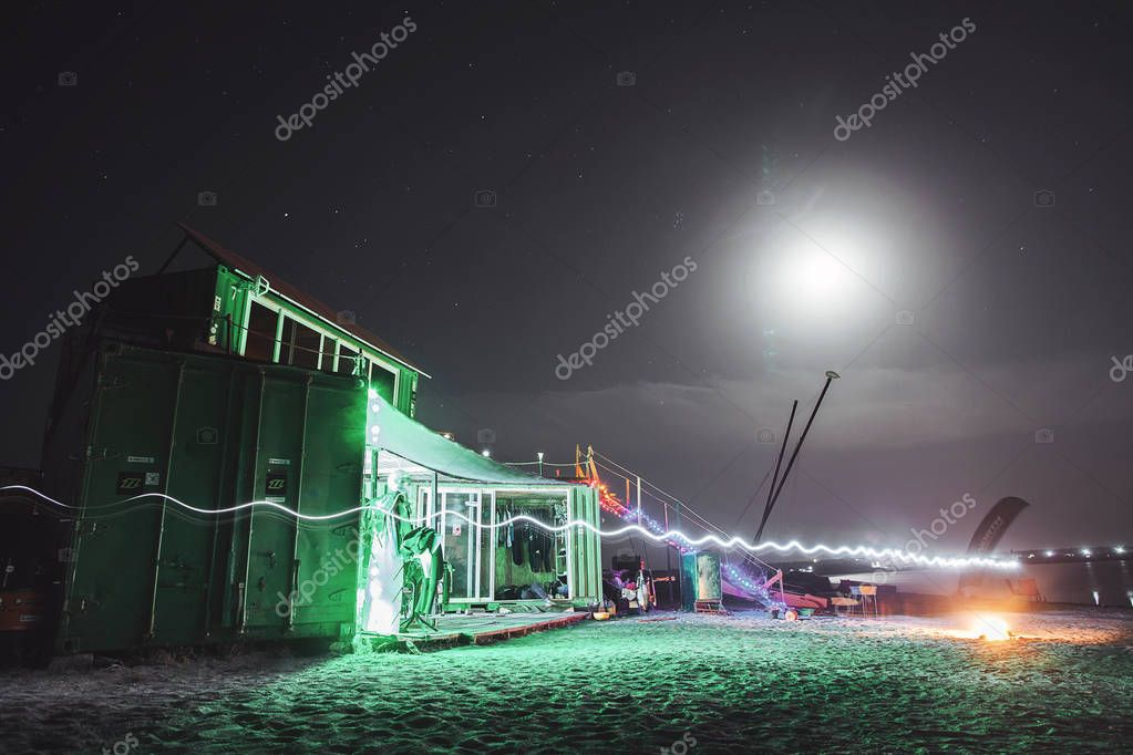 Container house at night on the shore. Youth disco.