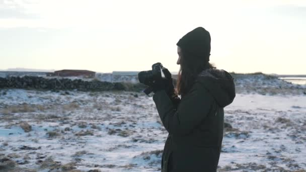 Travel girl takes a photo of winter Iceland