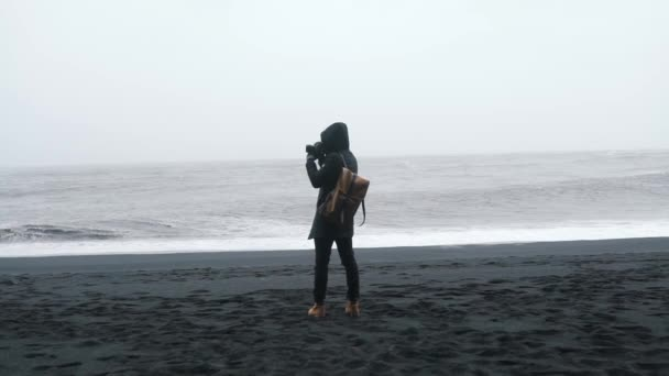Travel man with backpack takes a photo of stormy ocean