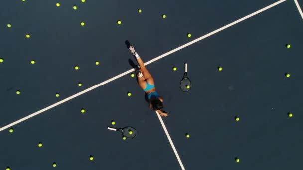 Hravá dívka leží na tenisový kurt