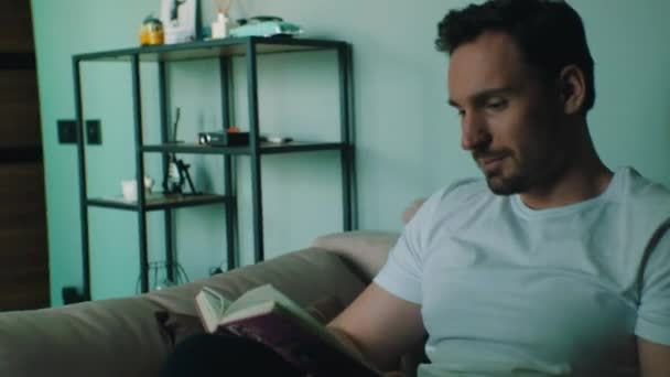 man reads a book while sitting at home