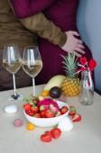Ein Paar trinkt Champagner mit liegenden Erdbeeren und exotischen Früchten. Valentinstag. Romantischer Abend.