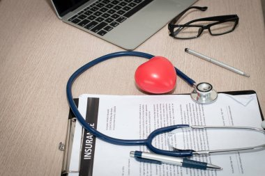 Workplace of doctor with laptop, stethoscope, small red heart  and glasses notebook on wooden table in the office.   Blood Pressure Monitor. Medical equipment. Cardiac diagnosis. vintage tone.
