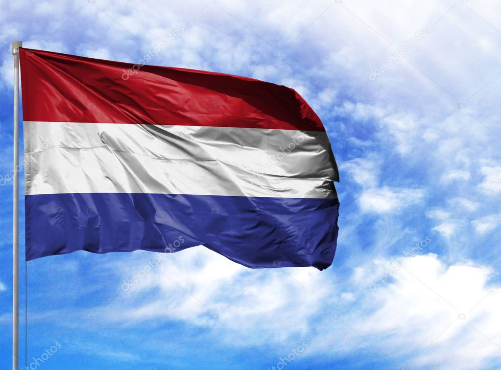 National flag of Netherlands on a flagpole in front of blue sky