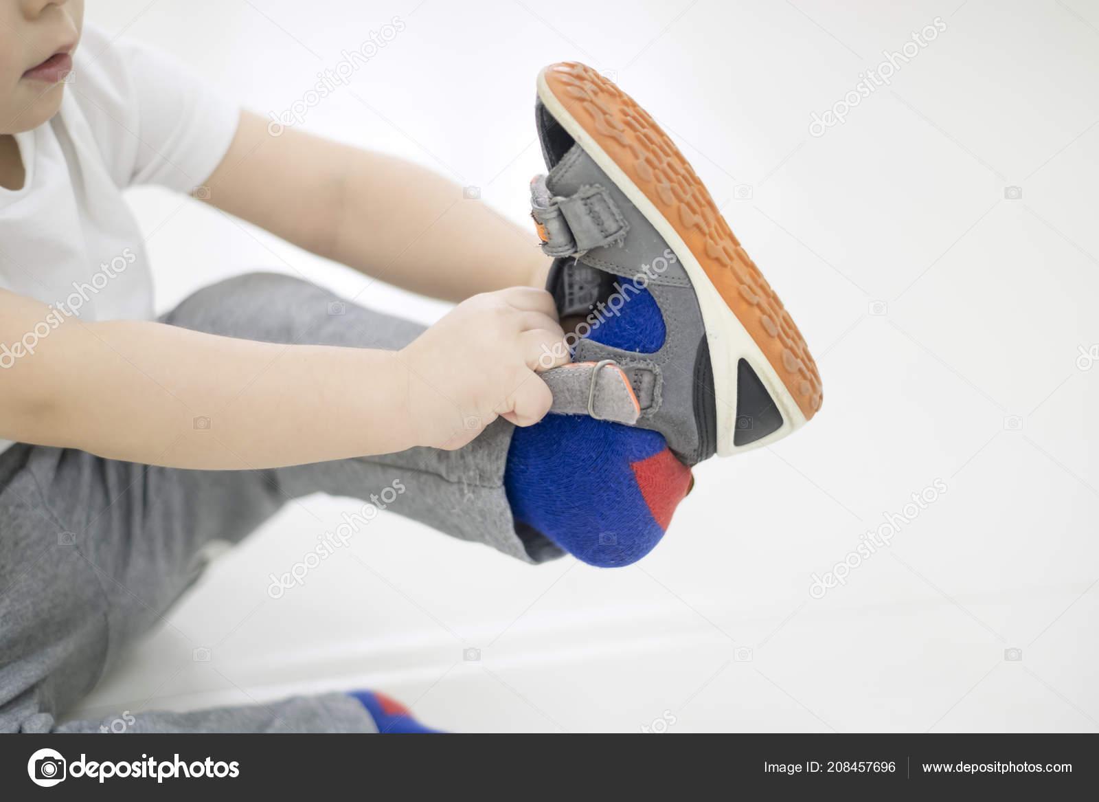 f81dfc3fe3135 Petit enfant tente de mettre sur ses chaussures. Bébé garçon avec des  chaussures à la main. Comment choisir ...