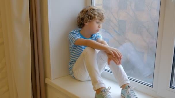 kudrnatý chlapec, který sedí na okenní parapetu, se dívá z okna. dítě ze šesti je smutné sedět samo v ložnici