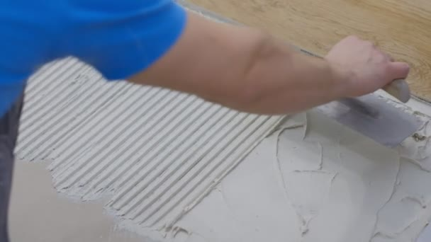 Professional worker laying tiles on floor at construction site close-up Builder puts concrete on floor.