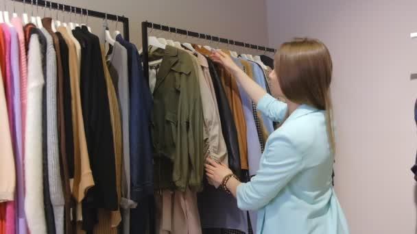 attraktives blondes Mädchen wählt Kleidungsstücke, die in Zeitlupe durch an Regalen hängende Muster schauen