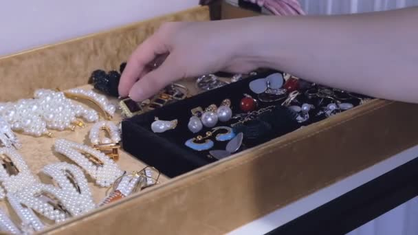 A young woman chooses earrings from her collection. fashion jewelry, beautiful accessories for every day.