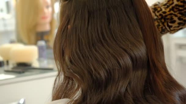 Ženská kadeřnice dělá pro klienta objemovitý účesu, který používá vlasové a ochlupené vlasy. Profesionální kadeřník v práci. Mistr dělá kadeřnictví dívku v salonu krásy, pomalý pohyb