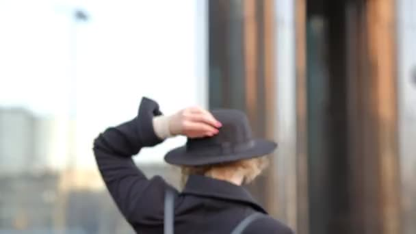 beautiful blond young woman in black hat smiles posing to camera looks upwards against building close view slow motion.