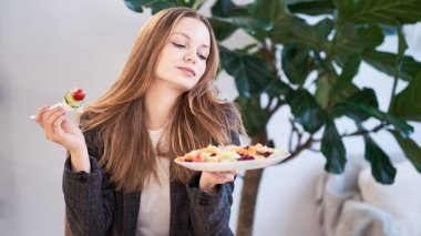 Woman in office eating salad at working place. Concept of lunch at work and eating healthy food. healthy eating concept. business woman in a jacket having lunch at the office
