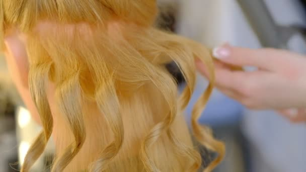 girl student hairdresser does hairstyle on dummy head with long blonde hair in light hairdressing salon