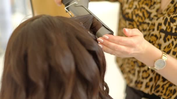 woman hairdresser marcels long brown hair with curling iron in light hairdressing salon backside view