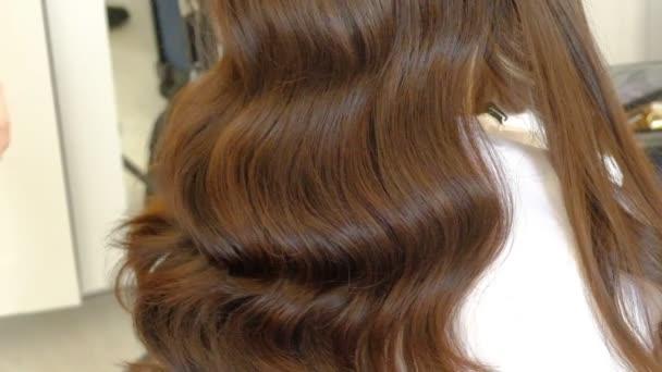 žena kadeřník marcels dlouhé hnědé vlasy s curling železo v lehkém kadeřnictví salon zadní pohled