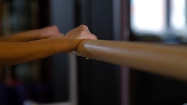 dívka profesionální tanečnice hezké ruce držet balet Barre dřevěné madlo před zrcadlem zavřít pohled pomalý pohyb.