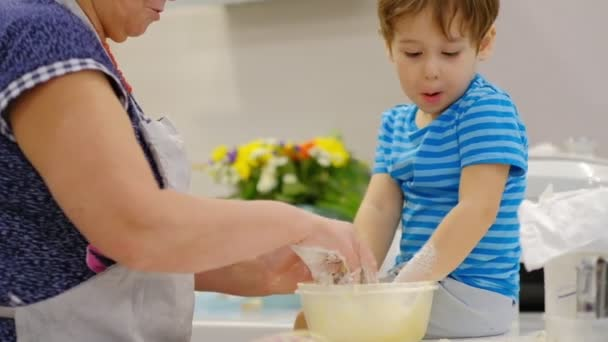 Close up of the happy smiled grandmother and grandson kneading a daugh together. slow motion of an elderly woman and little boy preparing pasta or pizza together.