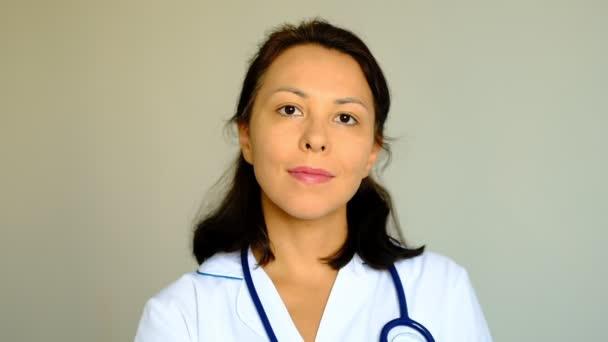 Pomalý pohyb zblízka na krásnou mladou ženu paní doktorka, která se dívá na kameru. Pojetí profese, medicíny a zdravotnictví, lékařské vzdělávání.