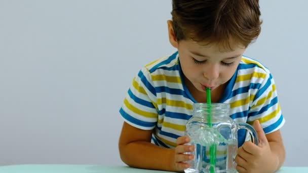Zeitlupe asiatisches süßes kleines Kind, das Wasser auf Küche trinkt. fröhlicher Junge bläst gerne Blasen