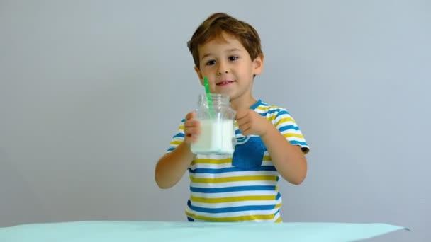 pomalý pohyb asijský roztomilá holčička pije mléko v kuchyni. Veselý hoch rád pije mléčný koktejl