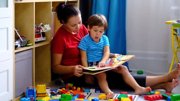 Happy mother and child son reading book. smiling mom baby sitter.