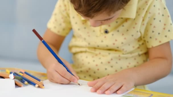 little cute boy draws with pencils. the child is engaged in creativity at home