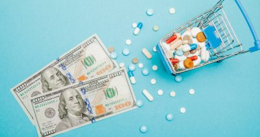 Dollars, pills and shopping cart on a blue background. Pharmacy concept. Copy space