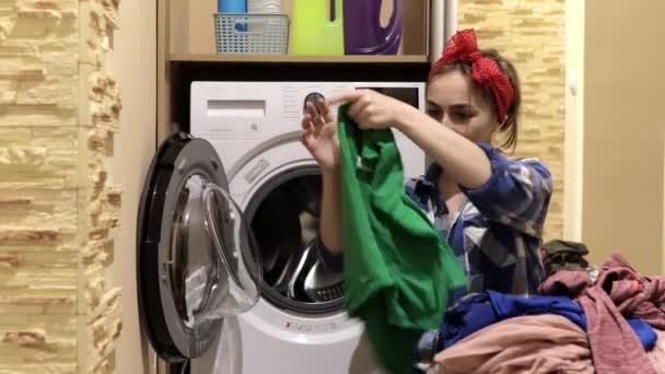 Eine Frau wäscht Kleidung. Eine Frau legt Kleidung in die Waschmaschine. Hausarbeit