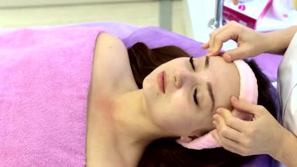 Relaxovaná žena ležící na lázeňském lůžku pro masážní ošetření obličeje a hlavy masážním terapeutem v luxusním lázeňském středisku. Wellness, stresová a omlazovací koncepce