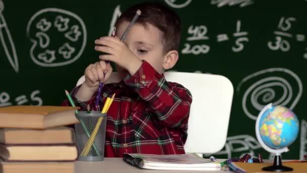 Az óvodás fiú házi feladatot csinál. Iskolás fiú boldog arckifejezéssel az íróasztal mellett, iskolai felszereléssel. Oktatás. Először az oktatás. Iskolai koncepció
