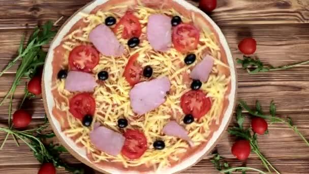 Syrová pizza s rajčaty, olivami a šunkou, italský styl na starém dřevěném stole, výhled shora