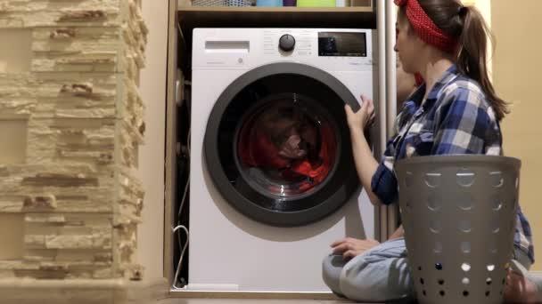 Egy nő ruhát mos. Egy nő ruhákat tesz a mosógépbe. Háztartási munka