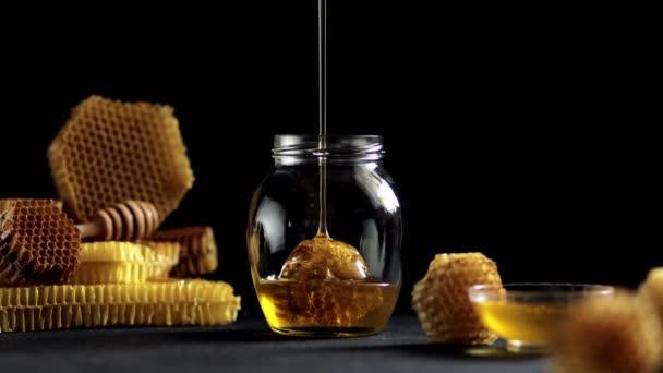 Med kape, vytéká z medu v dřevěné misce. Detailní záběr. Zdravý organický hustý med namáčený z dřevěné medové lžíce, detailní záběr. Videozáznam 4K UHD