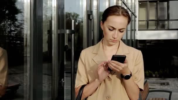 Kaukasische selbstbewusste junge Geschäftsfrau telefoniert draußen in der Nähe eines modernen Bürogebäudes