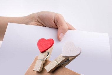 Hand holding a white sheet of paper with heart clips on it